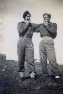 """גדוד 132, כפר יונה, תמונה ראשונה בצבא ! דב ליבוביץ' משמאל עם אלתר ויגדורוביץ', חבר יליד הונגריה כמוהו, מנגנים במפוחית. דב ניצול אושוויץ הגיע אחרי המלחמה למחנה העקורים בעיר בארי באיטליה שם גויס להגנה ועבר אימונים במשך 4 חודשים (גח""""ל). ב 25.4.48 עלה ארצה וחויל מיד, תחילה לגדוד הנפתי (132) ואח""""כ ל 35."""