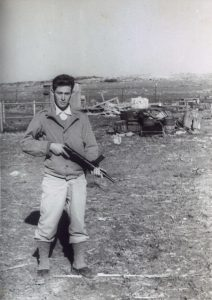 """דני רפאלי (1928-2012) במענית דצמבר 47. עם ראשית הגיוס הוצבה מח' של גד' 31 בפיקוד ישראל (שרולק'ה) כהן ליד קיבוץ מענית. כל הציוד על הגוף הוא פרטי: מעיל רוח אמריקאי, מכנסי חאקי אמריקאיות, גאטס מעל הנעליים, כנ""""ל, ו""""סטן"""" ביד. לאחר שבועיים שקטים במקום, שוחררה המח' הביתה."""