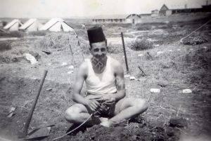 """כיתוב: בית ליד, 1948 סוף סוף, לראשונה, לאחר עזיבת הבריטים, נכנס הגדוד לבסיס קבע. זהו מחנה 20 הבריטי לשעבר שליד צומת בית ליד. כאן, יום טוב עם כובע וחרב """"שלל"""" מכיבוש סלמה."""
