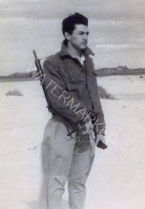 """כיתוב: """"משמר הים, ינואר 1948"""" מרדכי (מוטק'ה) קובל (קובלסקי), מדריך ספורט למתגייסים טריים בקבוץ משמר הים (אפק) ליד עכו. עכו ברקע."""